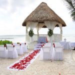 Tropical beach wedding location with rose petals scattered on the isle.
